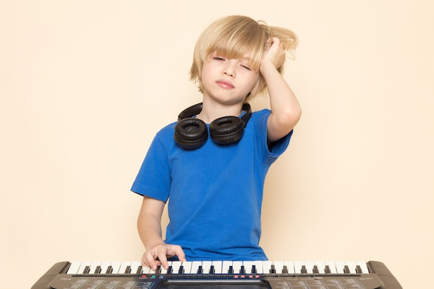 A front view cute little boy in blue t-shirt with black headphones playing little cute piano wanting sleep