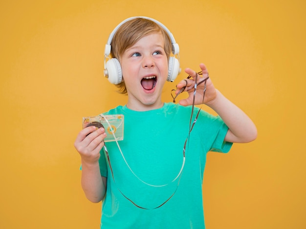 Front view of cute little boy listening to music