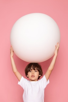 A front view cute little boy in white t-shirt playing with round white ball on the pink floor