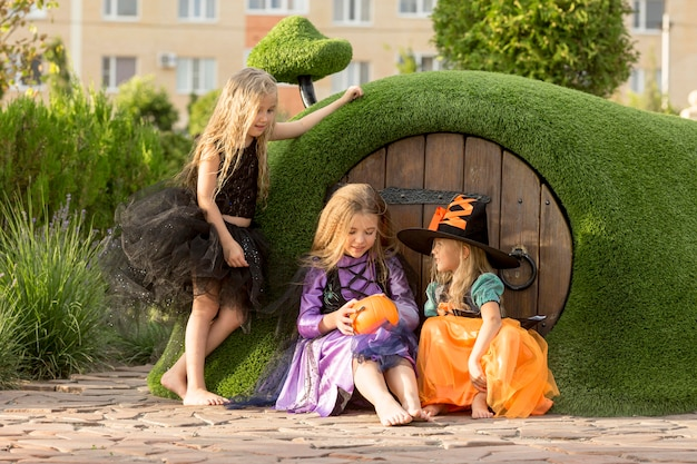 Front view of cute little girls with halloween costumes