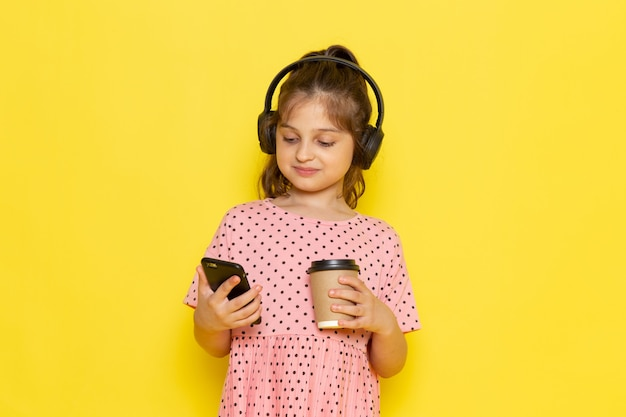 A front view cute little kid in pink dress holding and using phone listening to music with coffee on the yellow desk