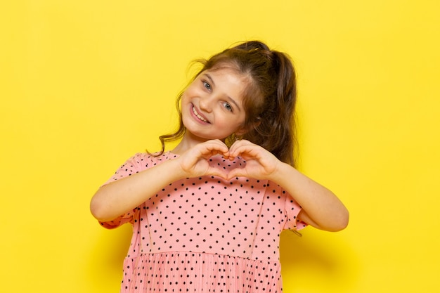 A front view cute little kid in pink dress smiling and showing love sign