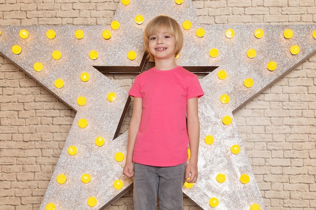 A front view cute little kid in pink t-shirt grey jeans smiling on the star designed yellow stand and light background