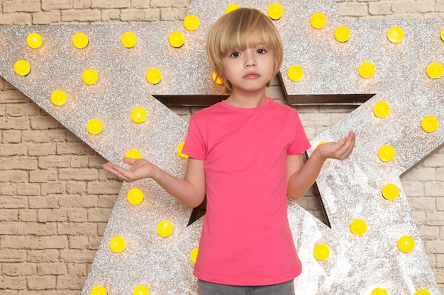 A front view cute little kid in pink t-shirt grey jeans on the star designed yellow stand and light background