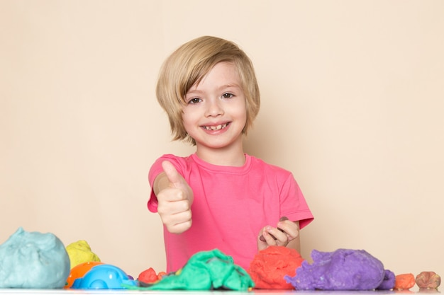 A front view cute little kid in pink t-shirt showing awesome sign playing with colorful kinetic sand