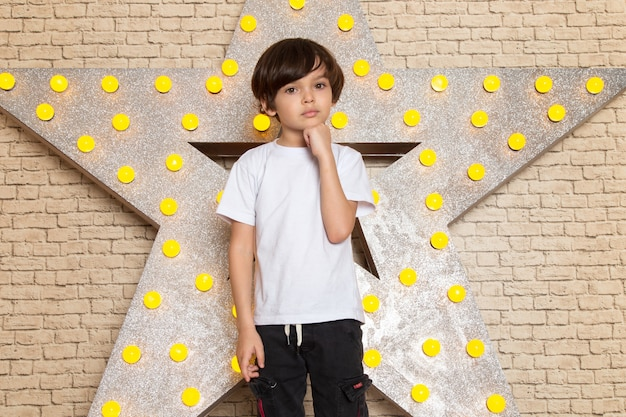 A front view cute little kid in white t-shirt dark jeans on the star designed yellow stand and light background