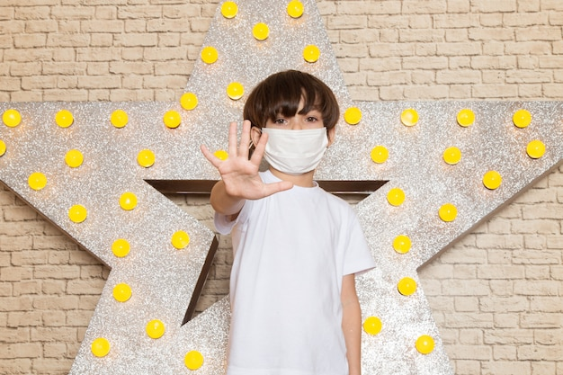 A front view cute little kid in white t-shirt dark jeans white sterile mask on the star designed yellow stand and light background