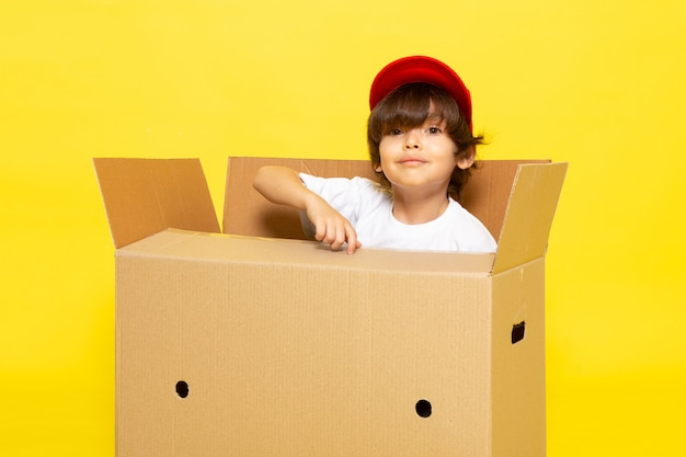 A front view cute little kid in white t-shirt red cap inside brown box on the yellow wall
