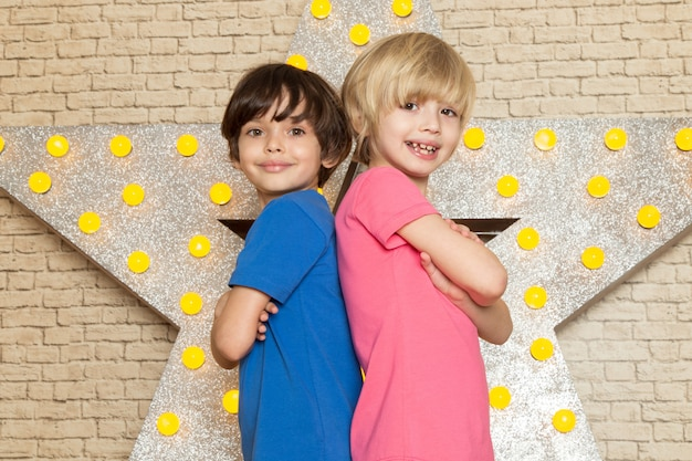 A front view cute little kids in blue and pink t-shirts dark and grey jeans on the star designed yellow stand and light background