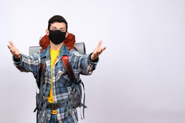 Viaggiatore maschio carino vista frontale con zaino e maschera che apre le mani per abbracciare