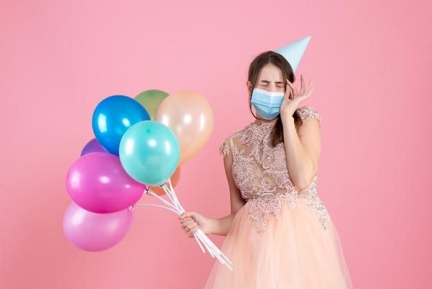 カラフルな風船を持って目を閉じるパーティーキャップと医療マスクと正面図かわいいパーティーの女の子
