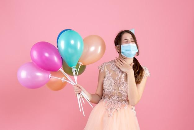 다채로운 풍선을 들고 눈을 감고 파티 모자와 전면보기 귀여운 파티 소녀