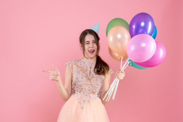 指で何かを指している風船を保持しているパーティーキャップを持つ正面図かわいいパーティーガール