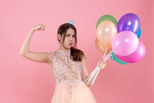 彼女の筋肉を示す風船を保持しているパーティーキャップを持つ正面図かわいいパーティーガール