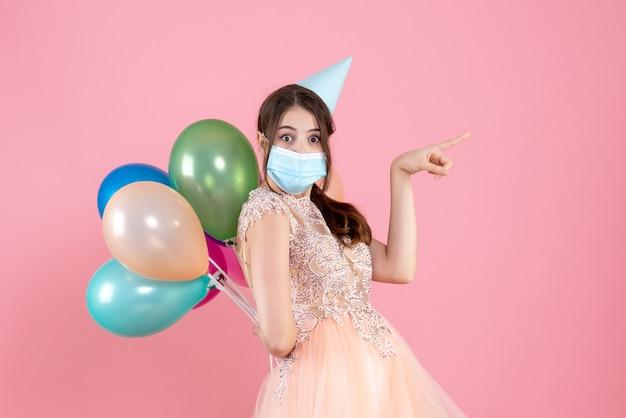 何かを指している彼女の背中の後ろにカラフルな風船を保持しているパーティーキャップを持つ正面図かわいいパーティーガール