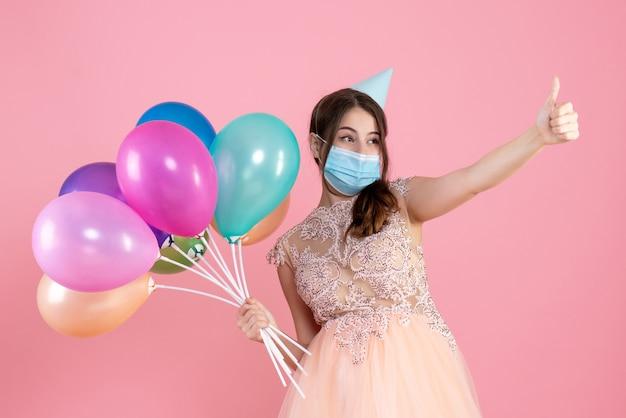 親指を立てるサインを作るカラフルな風船を保持しているパーティーキャップと正面図かわいいパーティーの女の子