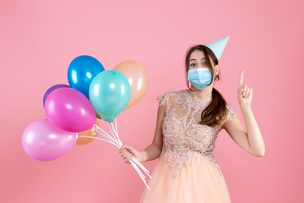 Front view cute party girl with party cap holding colorful balloons pointing with finger up