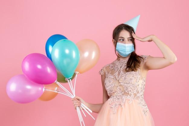 彼女の寺院に手を置くカラフルな風船を保持しているパーティーキャップを持つ正面図かわいいパーティーの女の子