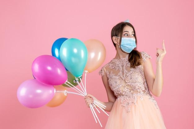カラフルな風船が立っているパーティーキャップを持つ正面図かわいいパーティーの女の子