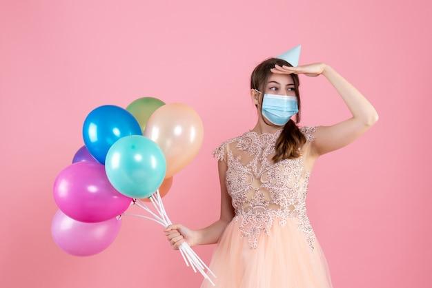 Ragazza carina festa di vista frontale con cappello da festa e mascherina medica che tiene palloncini colorati mettendo la mano sulla fronte