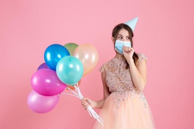 Ragazza carina festa di vista frontale con cappello da festa e mascherina medica che tiene palloncini colorati