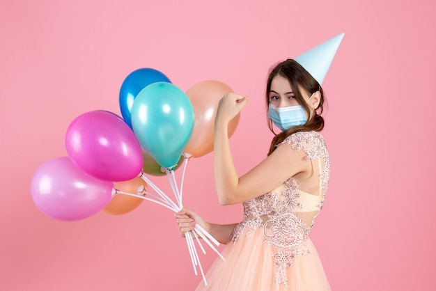 Front view cute party girl with party cap showing muscle holding colorful balloons standing