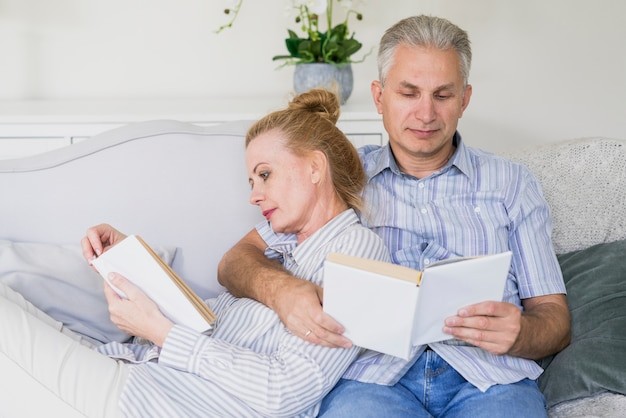Front view cute senior couple reading books