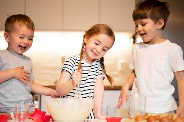 Front view of cute siblings cooking at home