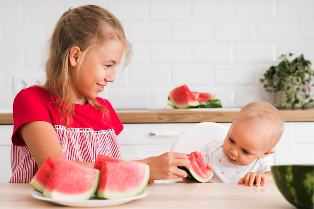Front view of cute sisters eating watermelon