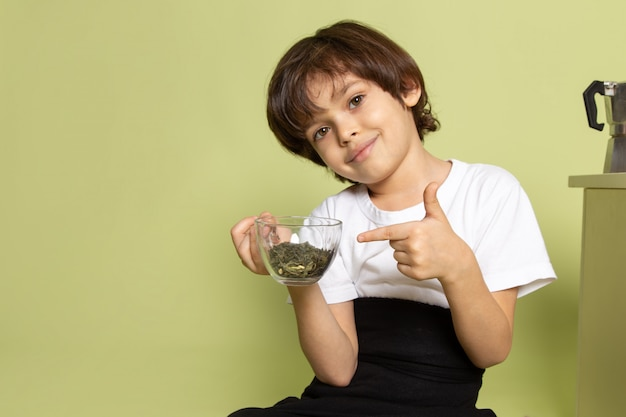 A front view cute smiling boy in white t-shirt holding species on the stone colored space