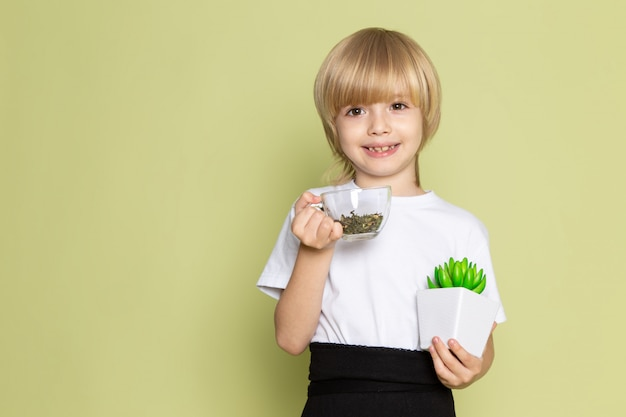 A front view cute smiling kid in white t-shirt holding species and green little plant on the stone colored desk