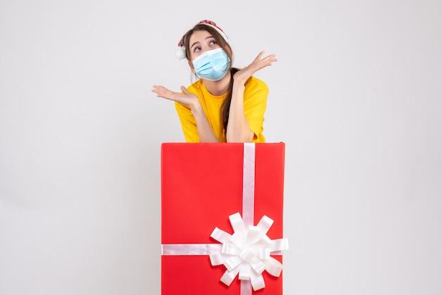 Вид спереди милая рождественская девушка в шляпе санта-клауса, открывая руки, стоя за большим рождественским подарком