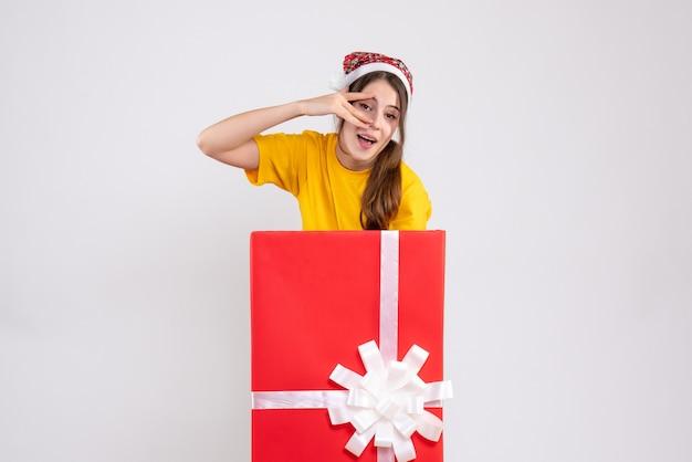 Вид спереди милая рождественская девушка в шляпе санта-клауса, стоящая за большим рождественским подарком