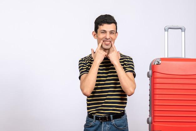 Вид спереди милый мальчик в полосатой футболке, указывая на его улыбку, стоящую возле чемодана
