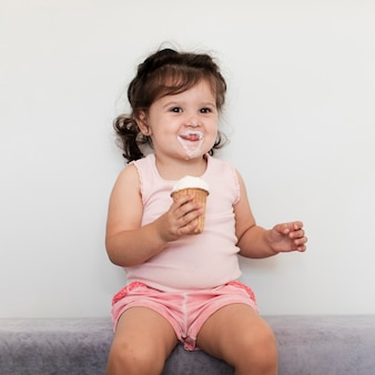 Front view cute young girl eating ice cream
