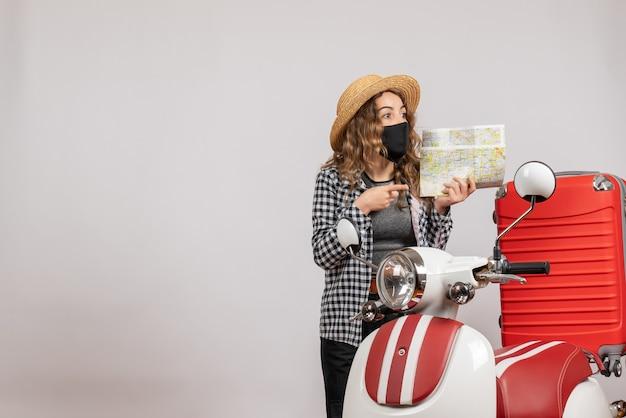 Vista frontale della ragazza carina con maschera nera che tiene la mappa in piedi vicino al ciclomotore rosso