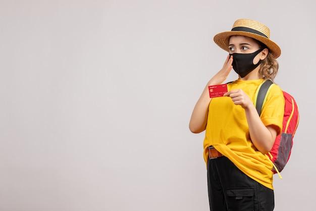 Vista frontale della giovane donna sveglia con lo zaino che sostiene la carta sul muro grigio