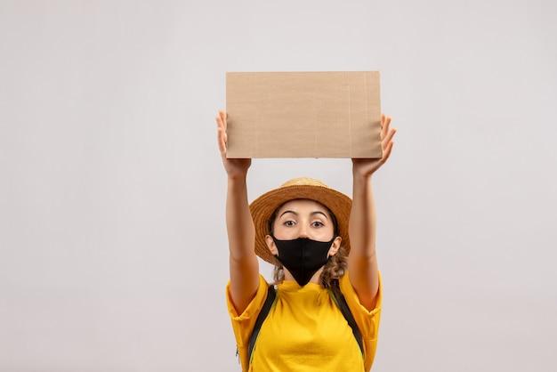 Vista frontale della giovane donna sveglia con lo zaino che porta la maschera nera che tiene cartone sulla parete bianca