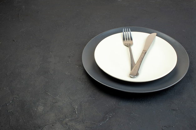 Front view of cutlery set on dark color and white empty plates in different sizes on black background