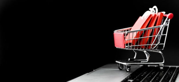 Front view of cyber monday shopping cart with bags and copy space