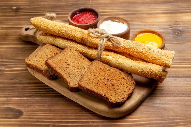 茶色のデスク食品パン パン スパイシーにパンと調味料を入れた正面図の暗いパン