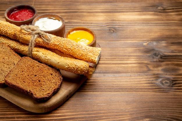 Vista frontale pagnotte di pane scuro con focacce e condimenti su panino di pane marrone da scrivania piccante