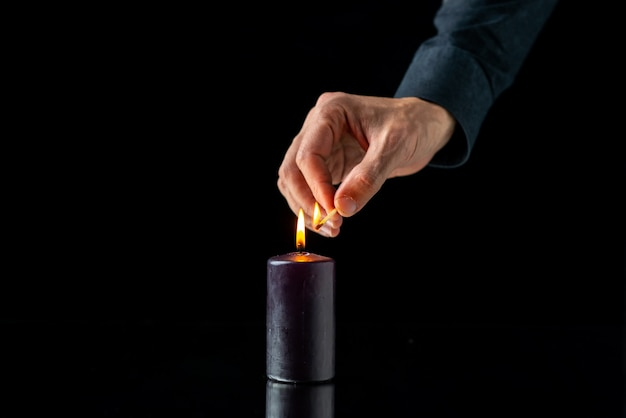 Front view of dark candle lighting on a dark surface