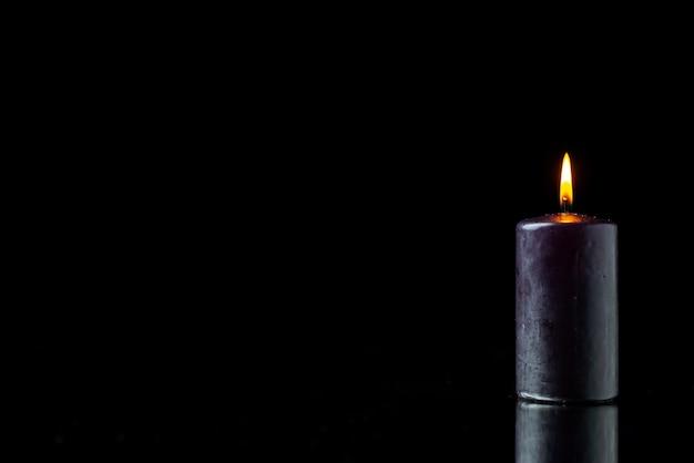 Vista frontale dell'illuminazione scura della candela sulla superficie scura