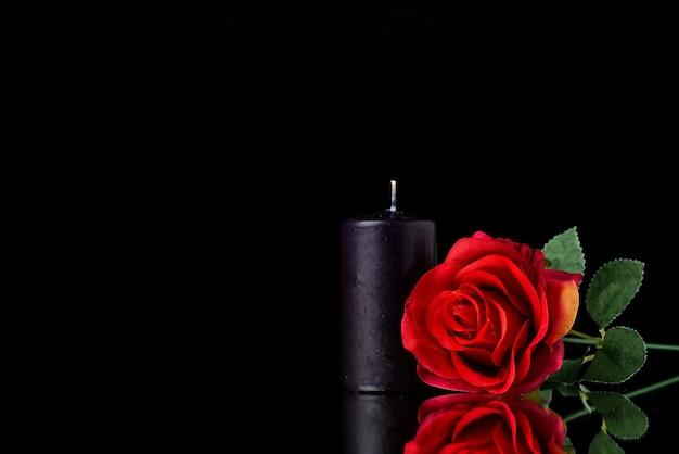 Vista frontale della candela scura con una rosa rossa sulla superficie nera
