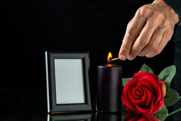 Front view of dark candle with red rose and picture frame on dark surface