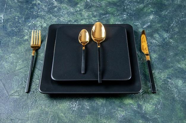 Vista frontale piatti scuri con cucchiai d'oro, forchetta e coltello su sfondo blu scuro