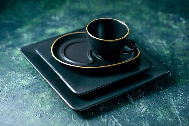 Vista frontale piatti quadrati scuri con tazza vuota su sfondo scuro