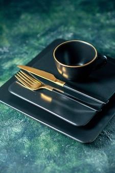 暗い背景に金色のフォークナイフとカップの正面図暗い正方形のプレート