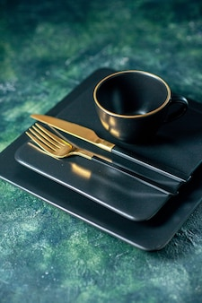 Front view dark square plates with golden fork knife and cup on dark background